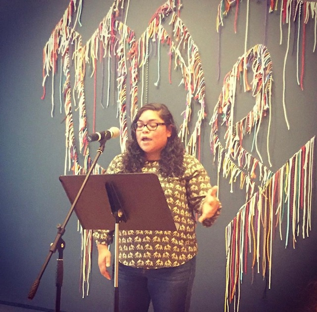 Noelia Cerna reading at Crystal Bridges in front of the We The People textile, 2019.
